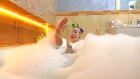 Het vrolijke donkerbruine meisje neemt schuimend bad en schrobt haar voet met een borstel 4k schot stock footage
