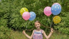 Het vrolijke en mooie meisje met kleurrijke ballen maakte aan haar haar en vlechten op haar hoofd vast Grappig idee met ballons Stock Foto's