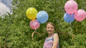 Het vrolijke en mooie meisje met kleurrijke ballen maakte aan haar haar en vlechten op haar hoofd vast Grappig idee met ballons Stock Fotografie