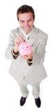 Het vrolijke geld van de zakenmanbesparing in een piggy-bank royalty-vrije stock foto