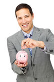 Het vrolijke geld van de zakenmanbesparing in een piggy-bank royalty-vrije stock afbeelding