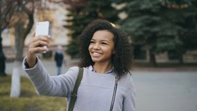 Het vrolijke gemengde meisje die van de rasstudent bij videovraag met smartphone dichtbij univercity spreken royalty-vrije stock afbeeldingen