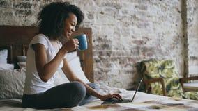 Het vrolijke gemengde rasmeisje typen op laptop computer voor het delen van sociale media die in bed thuis zitten Stock Foto's