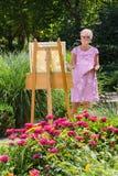 Het vrolijke hogere vrouw schilderen in tuin op zonnige dag stock foto