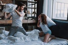 Het vrolijke Houdende van Paar bestrijdt Hoofdkussens in Bed stock foto