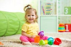 Het vrolijke jong geitje spelen in kinderdagverblijfruimte Stock Afbeeldingen
