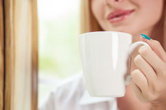 Het vrolijke jonge meisje drinkt hete koffie Royalty-vrije Stock Foto's