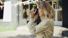Het vrolijke jonge meisje past camera aan die dan foto's van mooie stad nemen die zich in openlucht in de straat bevinden hobby stock videobeelden