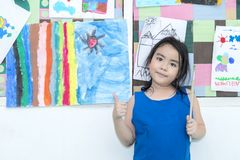 Het vrolijke jonge meisje schilderen op de muur, Kunstles stock foto