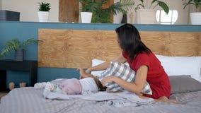 Het vrolijke jonge moeder spelen met dochter op bed in slaapkamer stock video
