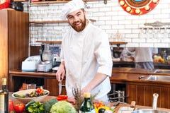 Het vrolijke jonge scherpe vlees van de chef-kokkok en het maken van plantaardige salade Stock Afbeeldingen