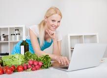 Het vrolijke jonge vrouw koken Stock Foto