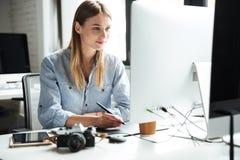 Het vrolijke jonge vrouwenwerk in bureau die computer met behulp van royalty-vrije stock afbeeldingen