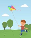 Het vrolijke jongen genieten die vlieger vliegen Stock Foto's