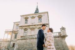 Het vrolijke jonggehuwdepaar houdt handen bij de achtergrond van het antieke gotische herenhuis Het beneden zijaanzicht stock fotografie