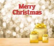 Het vrolijke Kerstmis 3d teruggevende rood schittert woord en gouden prese Stock Afbeelding