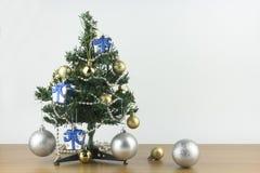 Het vrolijke Kerstmis en Nieuwjaarconcept, kleine Kerstboom is verfraaid met ornamenten op houten lijst en witte achtergrond stock foto