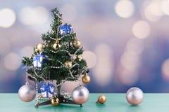Het vrolijke Kerstmis en Nieuwjaarconcept, kleine Kerstboom is verfraaid met ornamenten op lijst en bokeh blauwe toonachtergrond royalty-vrije stock foto