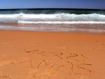 Het vrolijke Kerstmis van letters voorzien op het strand Stock Foto's