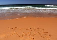 Het vrolijke Kerstmis van letters voorzien op het strand Royalty-vrije Stock Afbeeldingen