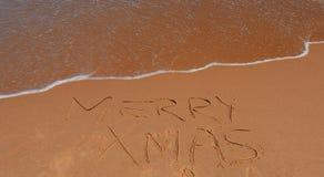 Het vrolijke Kerstmis van letters voorzien op het strand Stock Foto
