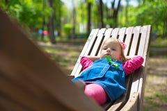 Het vrolijke kind ligt op houten bank in een zonnige dag stock foto's