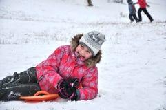 Het vrolijke kind sledding Stock Afbeeldingen