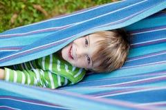 Het vrolijke kind spelen in blauwe hangmat Stock Fotografie