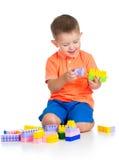 Het vrolijke kindjongen spelen met bouw die over wit wordt geplaatst Royalty-vrije Stock Foto's