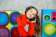 Het vrolijke kindmeisje luistert aan een lied met hoofdtelefoons Concept m Stock Afbeelding