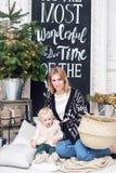 Het vrolijke mamma omhelst haar leuke babydochter Ouder en weinig kind die pret hebben dichtbij Kerstboom binnen loving royalty-vrije stock afbeelding