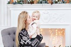 Het vrolijke mamma omhelst haar leuke babydochter Ouder en weinig kind die pret hebben dichtbij Kerstboom binnen loving stock foto's