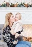 Het vrolijke mamma omhelst haar leuke babydochter Ouder en weinig kind die pret hebben dichtbij Kerstboom binnen loving stock afbeeldingen