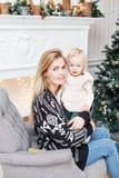 Het vrolijke mamma omhelst haar leuke babydochter Ouder en weinig kind die pret hebben dichtbij Kerstboom binnen loving royalty-vrije stock fotografie