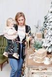 Het vrolijke mamma omhelst haar leuke babydochter Ouder en weinig kind die pret hebben dichtbij Kerstboom binnen loving royalty-vrije stock afbeeldingen