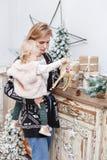Het vrolijke mamma omhelst haar leuke babydochter Ouder en weinig kind die pret hebben dichtbij Kerstboom binnen loving royalty-vrije stock foto's