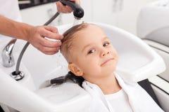 Het vrolijke mannelijke die kind heeft haar in salon wordt gewassen Stock Afbeeldingen