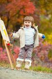 Het vrolijke meisje in een sprong met een borstel en een verf, trekt in het park van de herfstbladeren, het schilderen van het Kl Royalty-vrije Stock Foto's