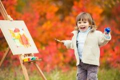 Het vrolijke meisje in een sprong met een borstel en een verf, trekt in het park van de herfstbladeren, het schilderen van het Kl Royalty-vrije Stock Foto
