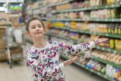 Het vrolijke meisje in een supermarkt toont op producten Een meisje van 8 jaar in een supermarkt stock afbeelding