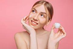 Het vrolijke meisje houdt een vochtinbrengende crème in haar hand en past het op haar gezicht toe om de huid te bevochtigen en ri stock afbeeldingen