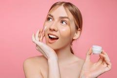 Het vrolijke meisje houdt een vochtinbrengende crème in haar hand en past het op haar gezicht toe om de huid te bevochtigen en ri royalty-vrije stock foto's