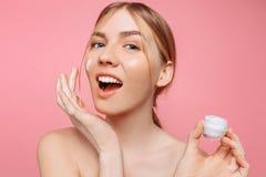 Het vrolijke meisje houdt een vochtinbrengende crème in haar hand en past het op haar gezicht toe om de huid te bevochtigen en ri royalty-vrije stock afbeelding
