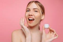 Het vrolijke meisje houdt een vochtinbrengende crème in haar hand en past het op haar gezicht toe om de huid te bevochtigen en ri royalty-vrije stock afbeeldingen