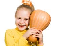 Het vrolijke meisje koestert een pompoen Royalty-vrije Stock Foto's