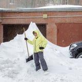 Het vrolijke meisje met de schop voor sneeuwverwijdering bevindt zich dichtbij een reusachtige sneeuwbank dichtbij de garage royalty-vrije stock foto's