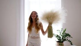 Het vrolijke meisje in pyjama springt met boeket van veergrassen in comfortabele atmosfeer, vrije allergie stock video