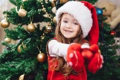 Het vrolijke meisje in rode hoed houdt een boomdecoratie Royalty-vrije Stock Afbeelding