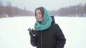 Het vrolijke meisje spreekt telefonisch, op de straat in de winter Langzame Motie stock footage