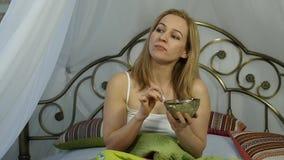 Het vrolijke meisje van de blondevrouw ontwaakte en etend een heerlijke salade op een bed, gezonde ontbijt langzame motie stock videobeelden